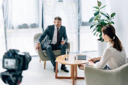Photo pour Foyer sélectif de journaliste parlant avec beau homme d'affaires en costume et lunettes - image libre de droit