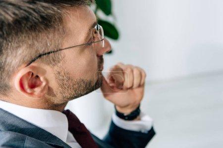 Photo pour Vue recadrée de l'homme d'affaires en costume et lunettes regardant loin dans le bureau - image libre de droit