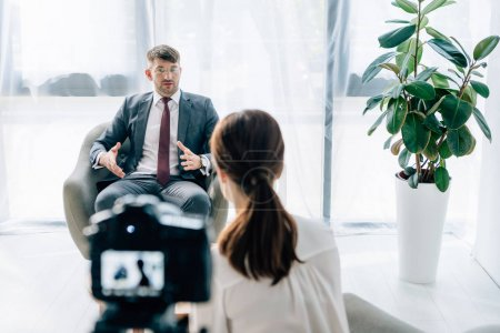 selective focus of handsome businessman in suit and glasses talking with journalist