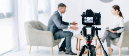Photo pour Mise au point sélective de journaliste de tir caméra numérique et homme d'affaires - image libre de droit