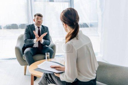 Photo pour Foyer sélectif de bel homme d'affaires en costume et lunettes parler avec le journaliste - image libre de droit