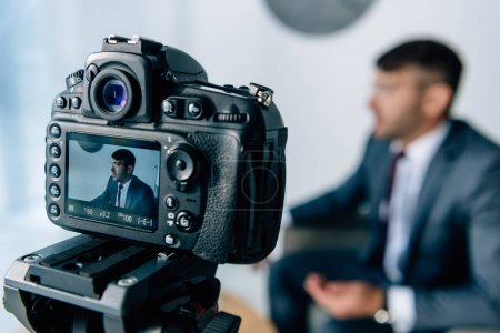 selective focus of digital camera shooting businessman in suit