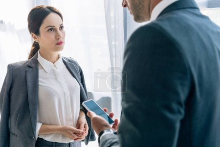 selective focus of attractive journalist talking with businessman in formal wear