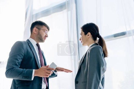 Photo for Journalist talking with handsome businessman in formal wear and glasses - Royalty Free Image
