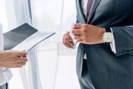 vue recadrée du dossier de tenue de journaliste et homme d'affaires avec smartphone