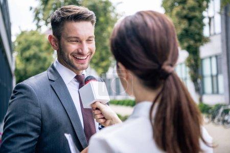 Journalist hält Mikrofon in der Hand und spricht mit Geschäftsmann in offizieller Kleidung
