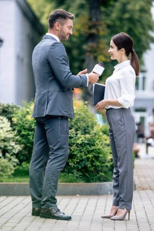 Photo for Journalist holding microphone and talking with businesswoman in formal wear - Royalty Free Image