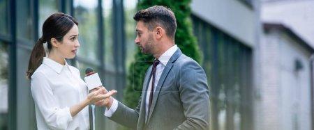 Photo pour Tir panoramique de journaliste tenant le microphone et parlant avec la femme d'affaires dans l'usure formelle - image libre de droit