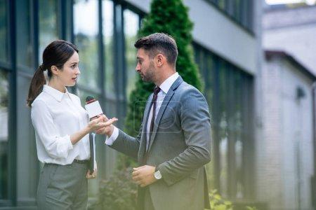 Foto de Periodista sosteniendo micrófono y hablando con empresaria en ropa formal - Imagen libre de derechos