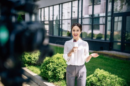 selective focus of attractive journalist holding microphone and speaking outside