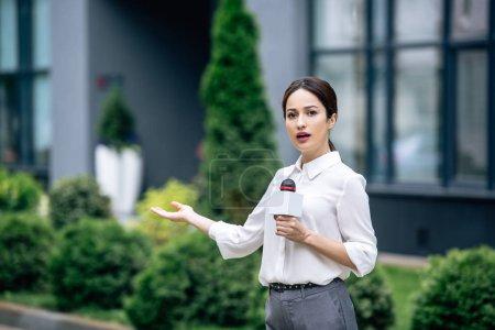 Photo pour Journaliste attrayant en tenue formelle tenant microphone et parlant à l'extérieur - image libre de droit