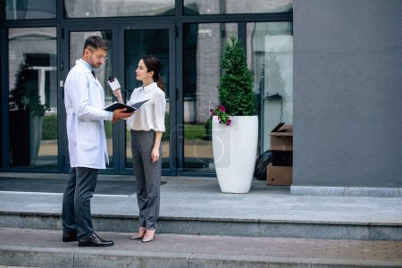 Photo for Journalist holding microphone and talking with handsome doctor in white coat - Royalty Free Image