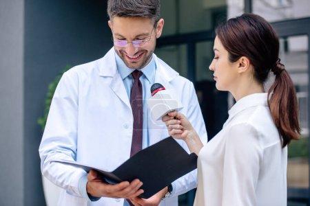 Photo pour Journaliste tenant un microphone et parlant avec beau médecin en manteau blanc - image libre de droit