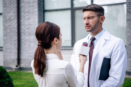journalist holding microphone and talking with handsome doctor in white coat