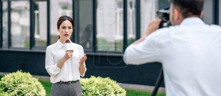 Photo pour Prise de vue panoramique de journaliste attrayant tenant microphone et caméraman tirant sur elle à l'extérieur - image libre de droit