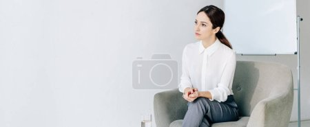 panoramic shot of attractive journalist in formal wear sitting in armchair
