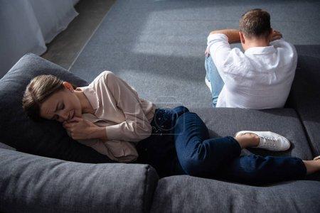 Foto de Llorando molesto mujer en el sofá y el hombre sentado en el suelo en la sala de estar - Imagen libre de derechos