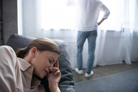 Photo for Upset woman crying on sofa and man standing near window - Royalty Free Image