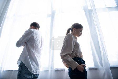 Photo pour Vue inférieure de la femme et de l'homme bouleversés dans des chemises restant près de la fenêtre - image libre de droit