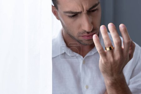 Photo for Depressed man in white shirt looking on ring on finger - Royalty Free Image