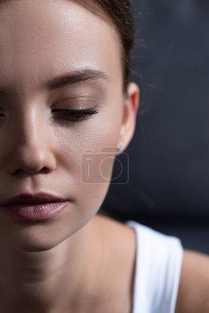 Photo pour Vue recadrée de jeune femme bouleversée avec les yeux fermés - image libre de droit