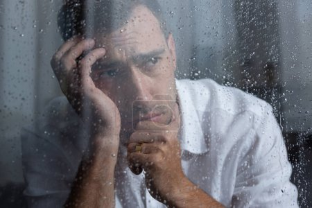 Photo for Selective focus of upset man looking away at home - Royalty Free Image