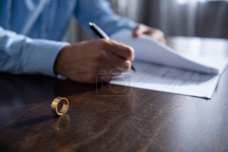 Photo pour Vue partielle de l'homme s'asseyant à la table et signant des documents de divorce - image libre de droit
