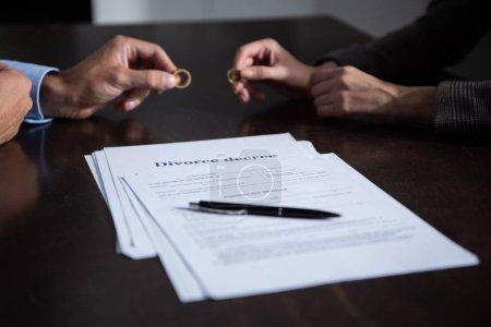 Foto de Vista parcial de la pareja en la mesa con documentos de divorcio que sostienen anillos - Imagen libre de derechos