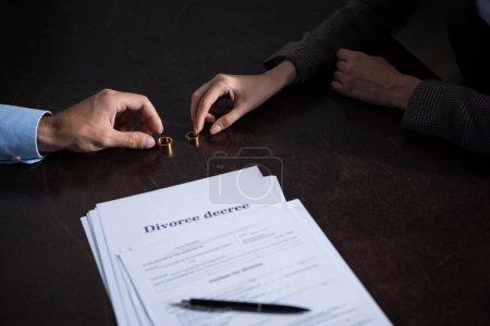 Foto de Vista parcial de la pareja en la mesa con documentos de divorcio y anillos - Imagen libre de derechos