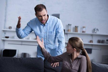 Foto de Agresivo hombre en camisa gritando a esposa durante pelea - Imagen libre de derechos