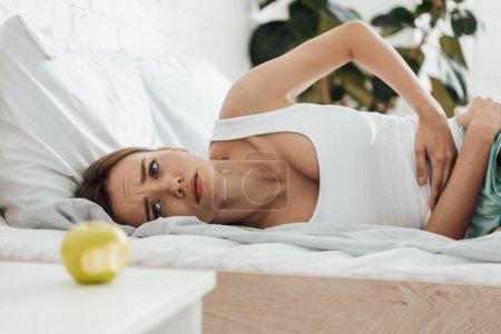 Foto de Mujer que sufre acostada en la cama, tocando el vientre y mirando a la manzana - Imagen libre de derechos