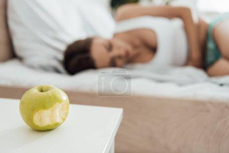Photo pour Foyer sélectif de souffrance femme touchant le ventre et pomme verte au premier plan - image libre de droit