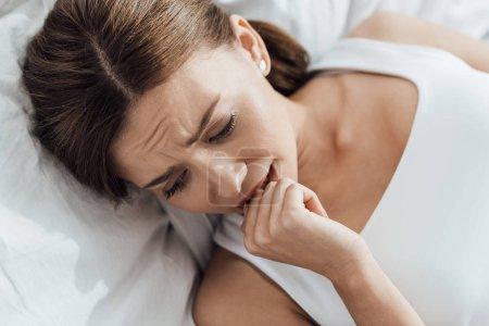 Photo pour Jeune femme stressée se trouvant sur le lit à la maison - image libre de droit