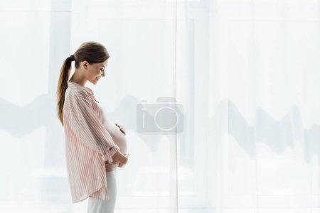 Foto de Vista lateral de la mujer embarazada feliz sonriendo y tocando el vientre - Imagen libre de derechos