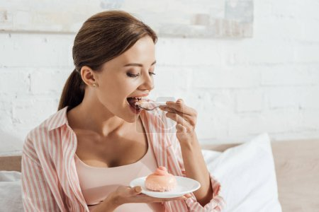 Photo for Pregnant woman sitting on bed and eating cupcake - Royalty Free Image