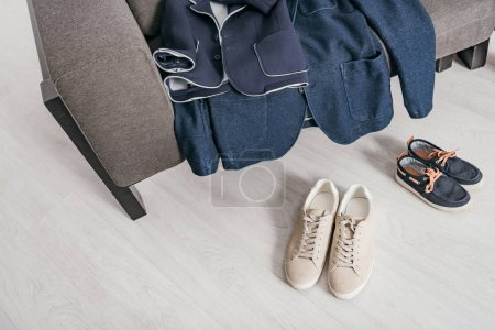 Photo for Formal jackets on sofa and shoes on floor at home - Royalty Free Image