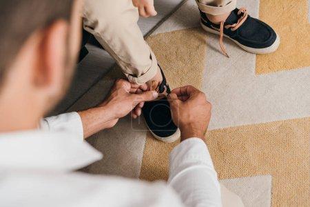 Foto de Vista recortada del padre atando cordones de zapatos para el hijo en casa - Imagen libre de derechos
