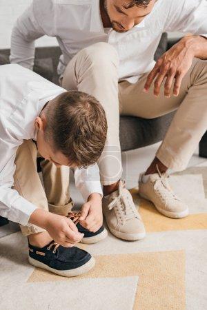 Photo pour Vue recadrée du père enseignant fils à attacher des lacets à la maison - image libre de droit