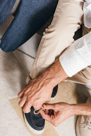 Photo pour Vue partielle du père enseignant le fils à attacher des lacets à la maison - image libre de droit