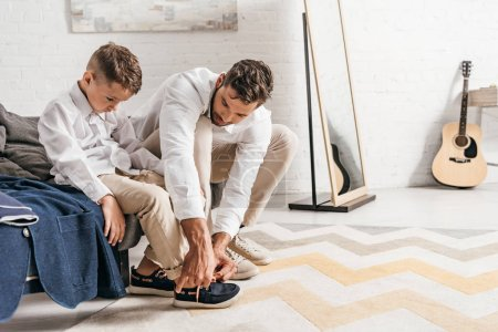 father teaching son to tying shoelaces at home