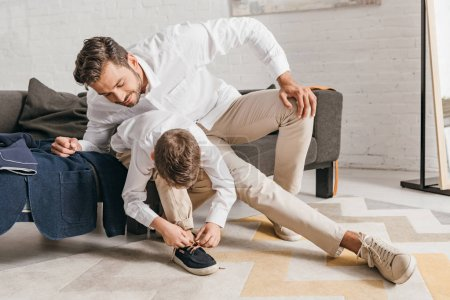 Photo for Father teaching son to tying shoelaces at home - Royalty Free Image