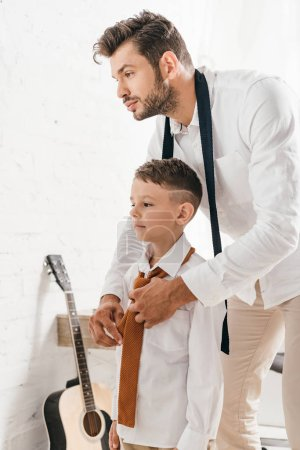 bearded dad helping son with tie at home