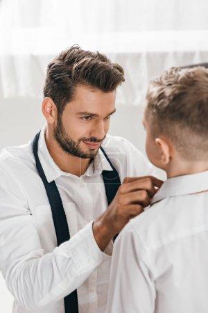 Photo pour Père souriant aidant le fils pour s'habiller à la maison - image libre de droit