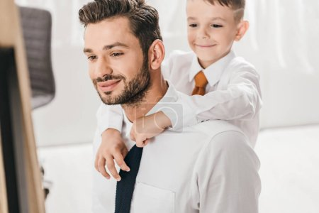 Photo for Cheerful boy embracing bearded dad in white shirt at home - Royalty Free Image