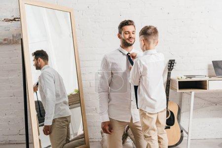 Photo pour Fils dans la chemise blanche aidant le papa avec la cravate à la maison - image libre de droit