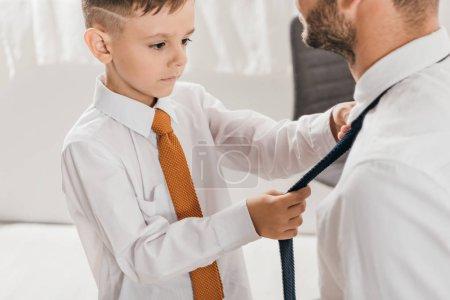 Photo pour Vue recadrée de fils dans la chemise blanche aidant le papa avec la cravate à la maison - image libre de droit