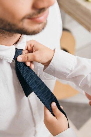 Photo pour Vue recadrée de fils en chemise blanche aidant papa avec cravate à la maison - image libre de droit