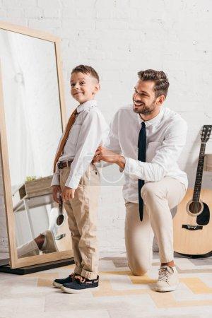 Photo pour Papa barbu aidant le fils à s'habiller à la maison - image libre de droit