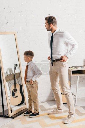 Photo pour Pleine longueur vue de fils et père dans l'usure formelle debout près du miroir - image libre de droit