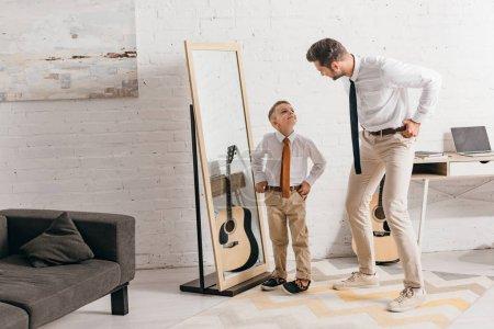Photo pour Vue pleine longueur du fils et du père dans l'usure formelle restant près du miroir et regardant l'un l'autre - image libre de droit